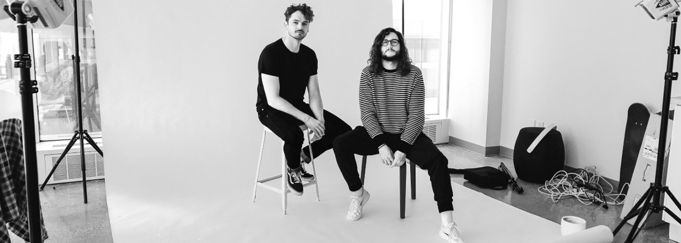 Two people sitting on stools in studio