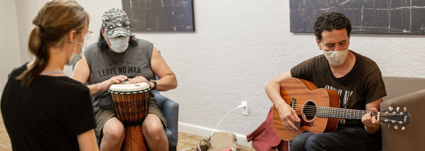 Photo of three people sitting together playing musical instraments