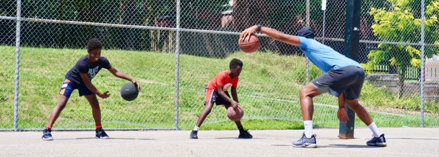 Man showing two children how to play basketball
